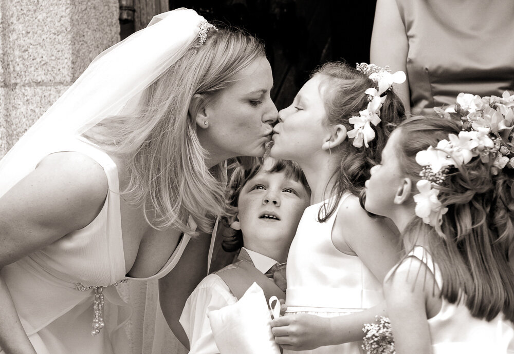 Bride with blonde hair leaning over to kiss a flower girl with flowers in her hair