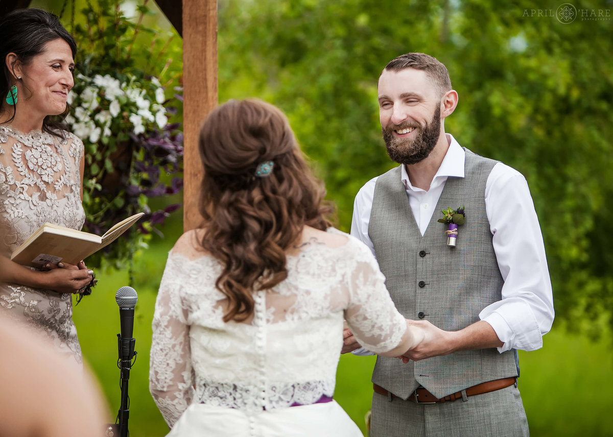Groom smiles at bride at their outdoor wedding at Denver Botanic Gardens Chatfield Farms