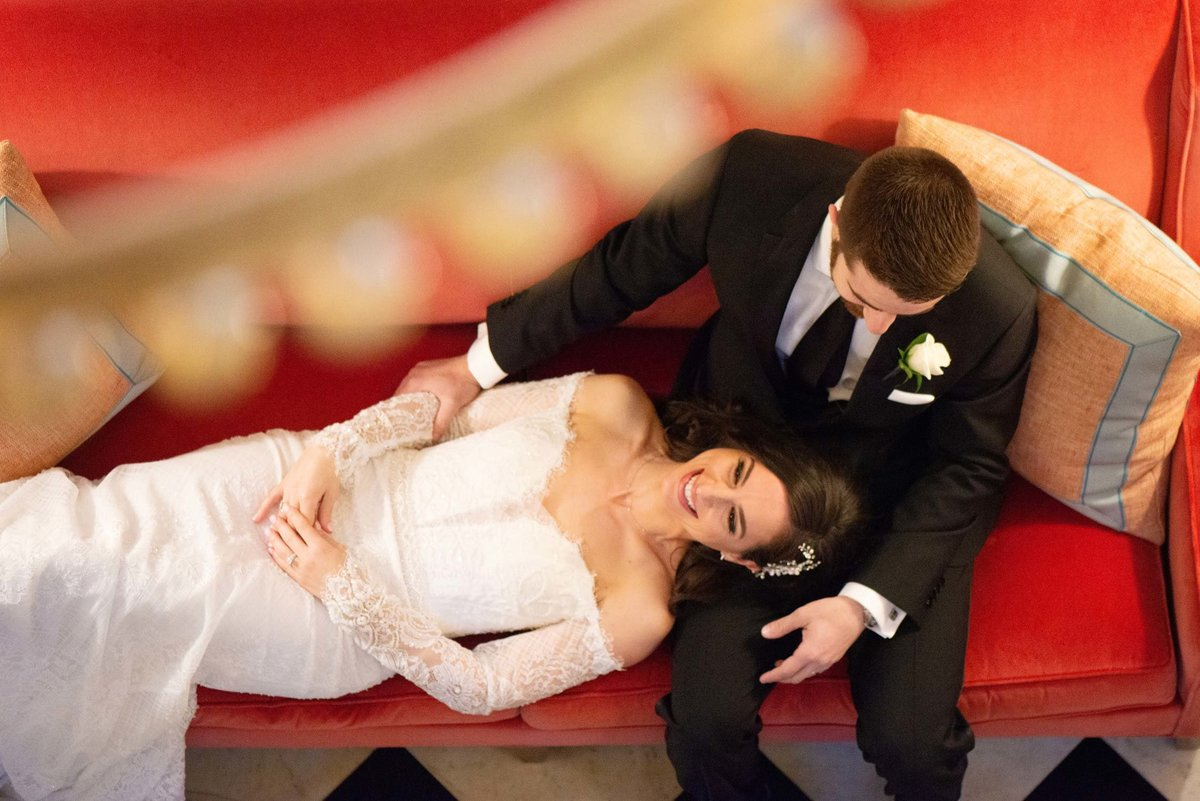 Top shot of bride and groom on the red softa at The Mansion at Oyster Bay
