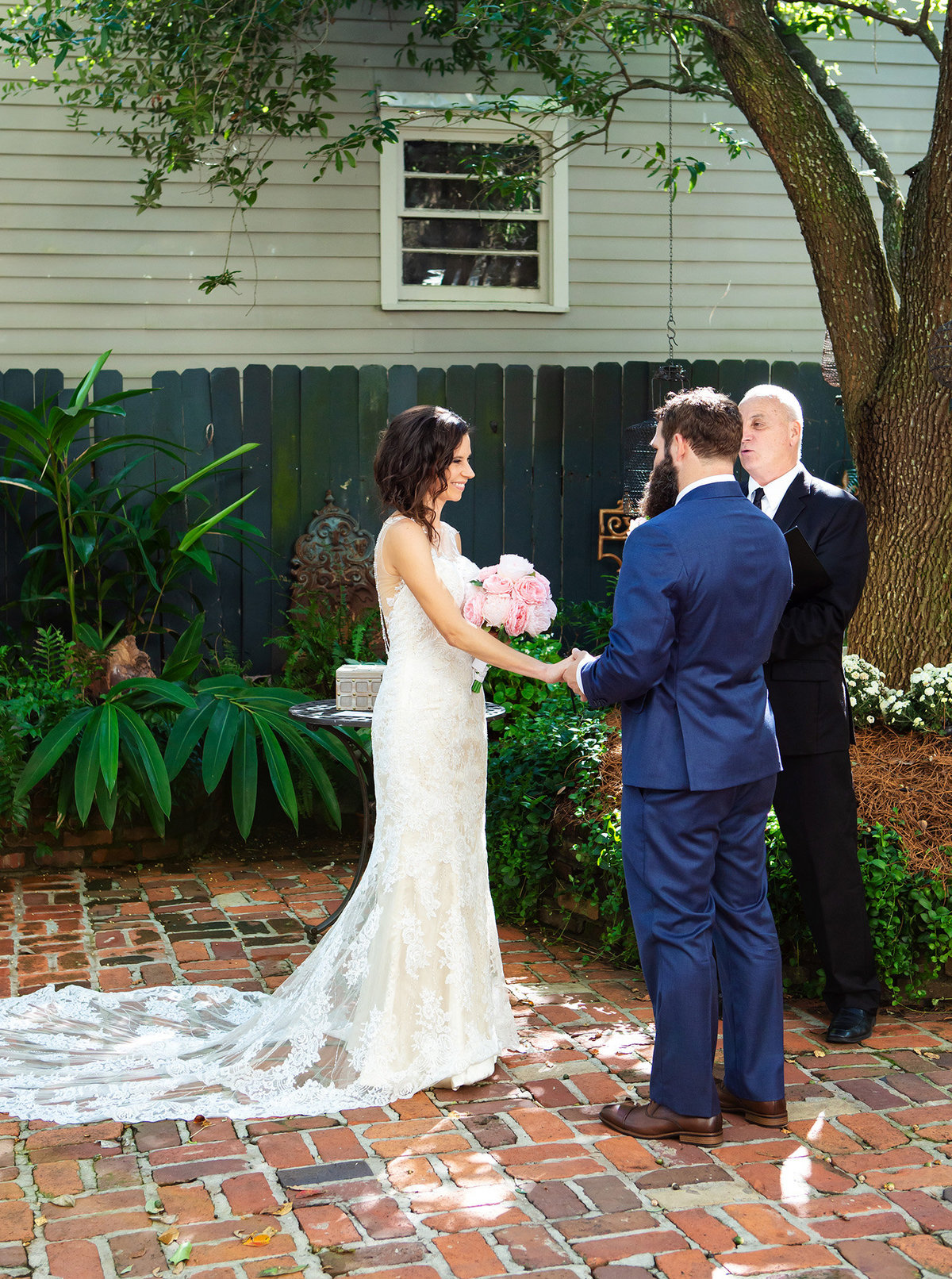 new orleans groom holds bride's hand as they say their vows in the courtyard of The Terrell House