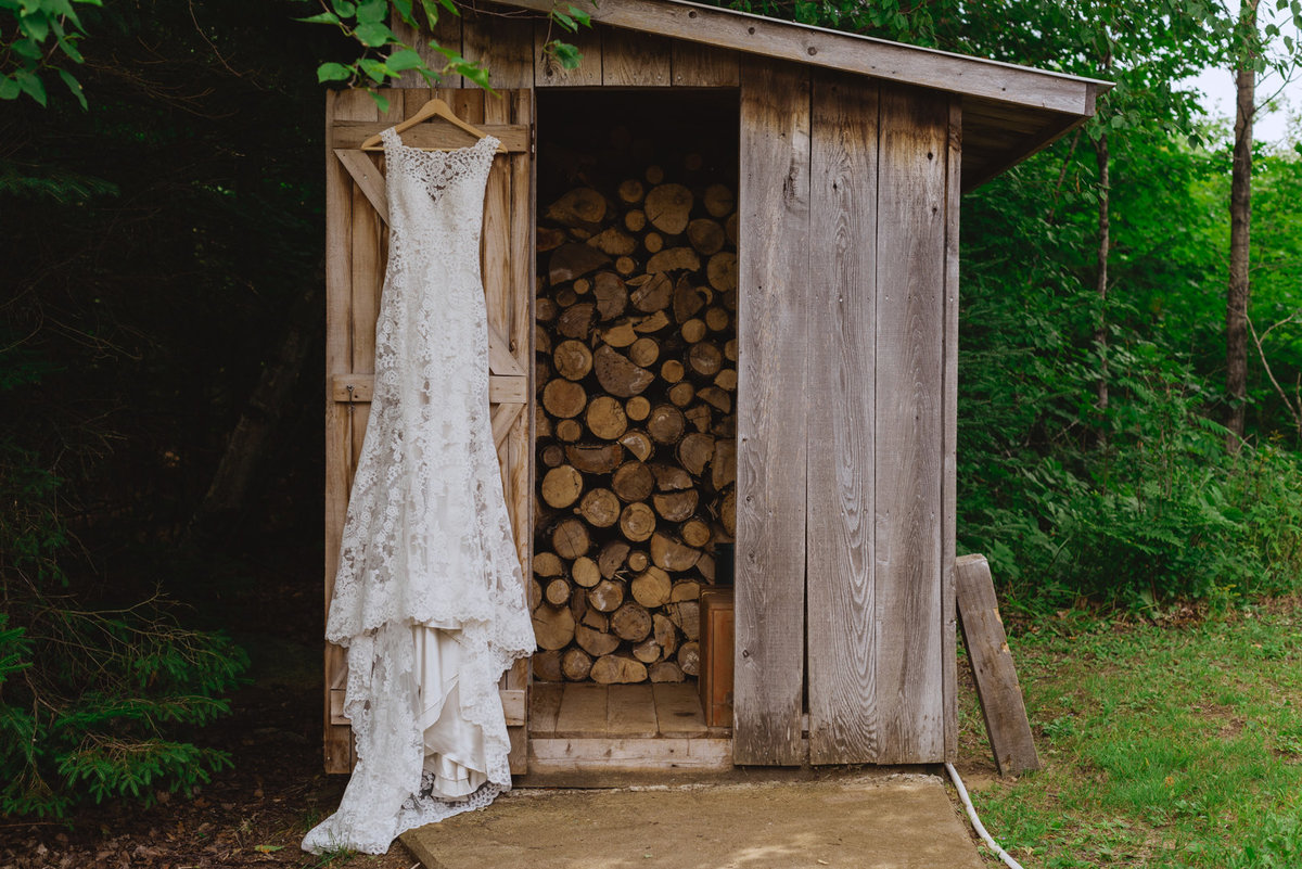 wedding dress hanging from woodshed