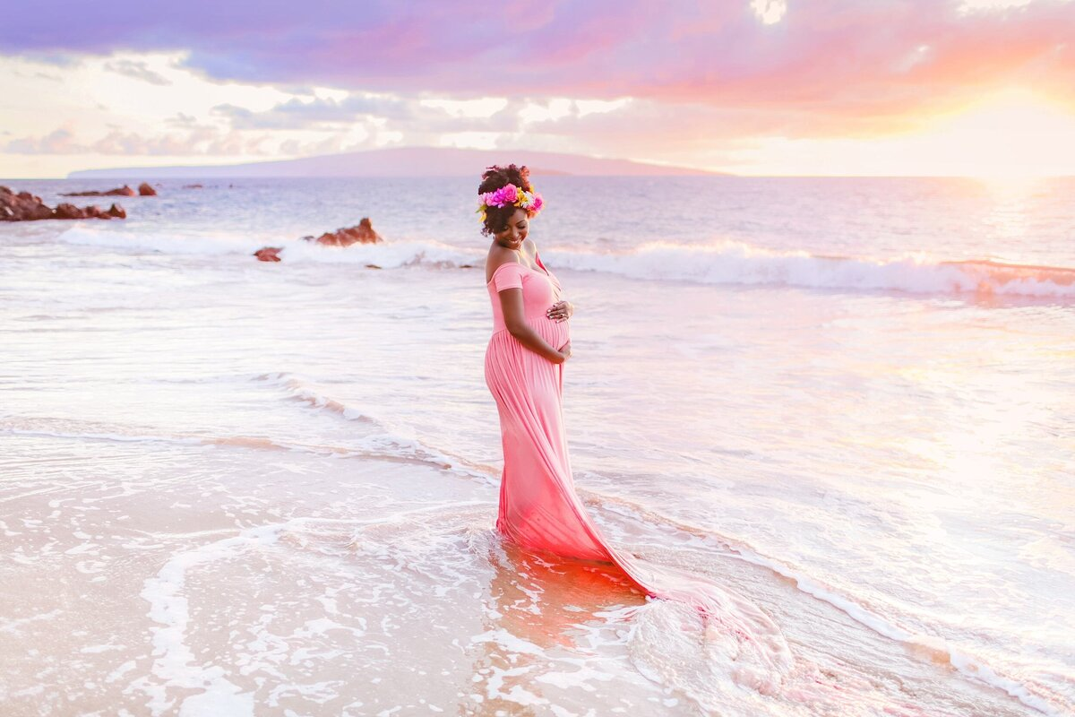 Woman wearing pink maternity gown photographed on the beach on Maui at sunset