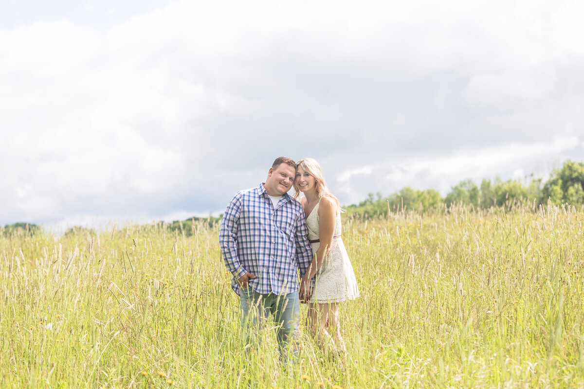 engaged couple standing in high grass farmhouse new jersey