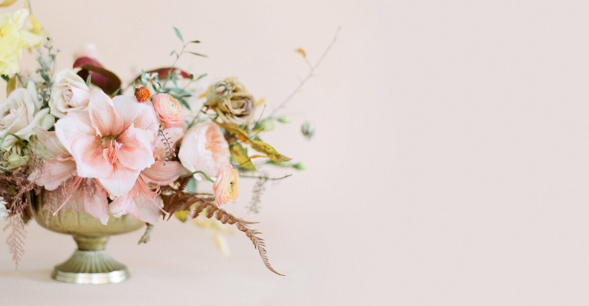 Flowing, textured floral still-life photograph of wedding centerpiece with blush flowers in a gold vase against a blush backdrop