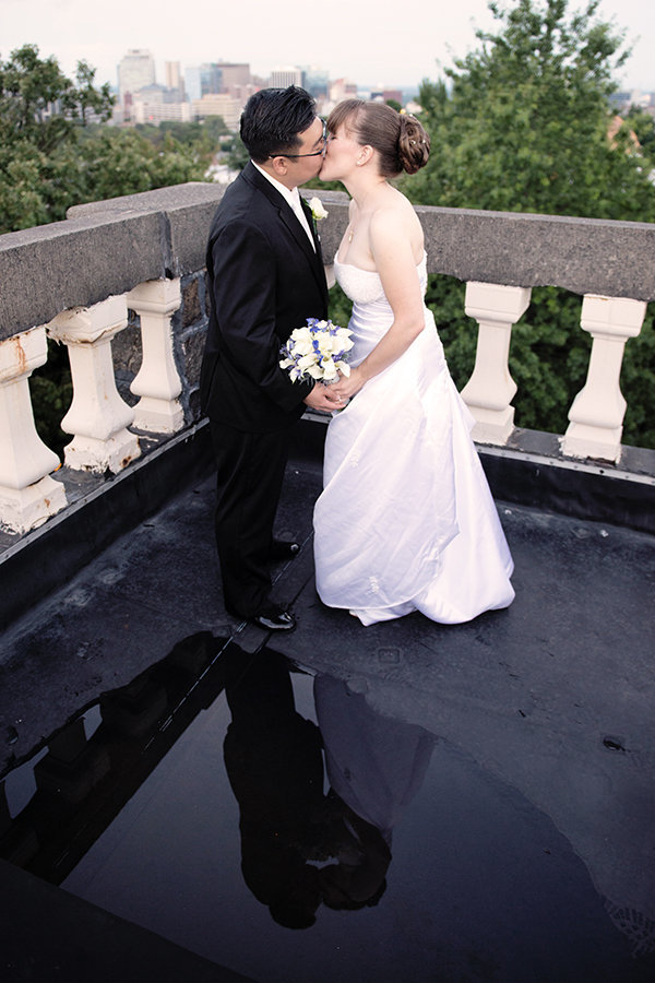 A bride and groom kiss on the rooftop of the historical University and Whist Club in Delaware