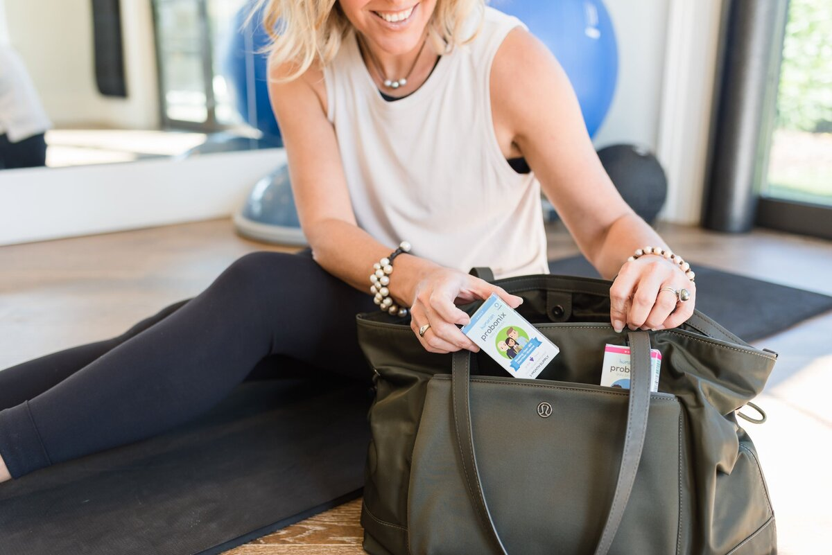 White woman pulling probiotics out of her green gym bag for a product photoshoot in Nashville