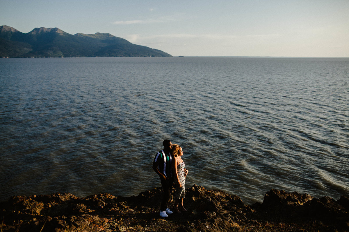 wide shot of couple along turnagain arm with view of the ocean