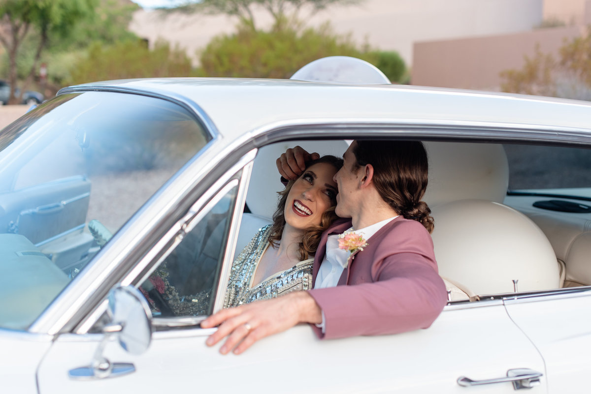 bride smiles at groom while sitting in a vintage car