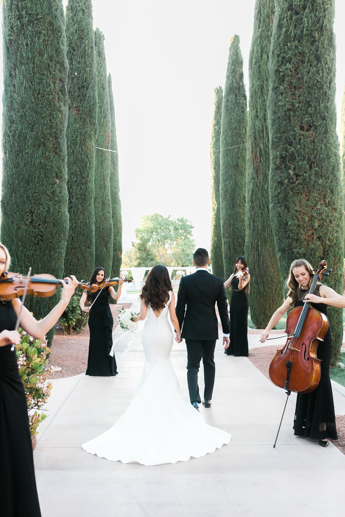 a photo of a bride and groom walking down a walkway lined with tall topiaries and a string quartet is lined serenading the couple for their wedding at Green Valley Ranch Resort and Spa in Las Vegas