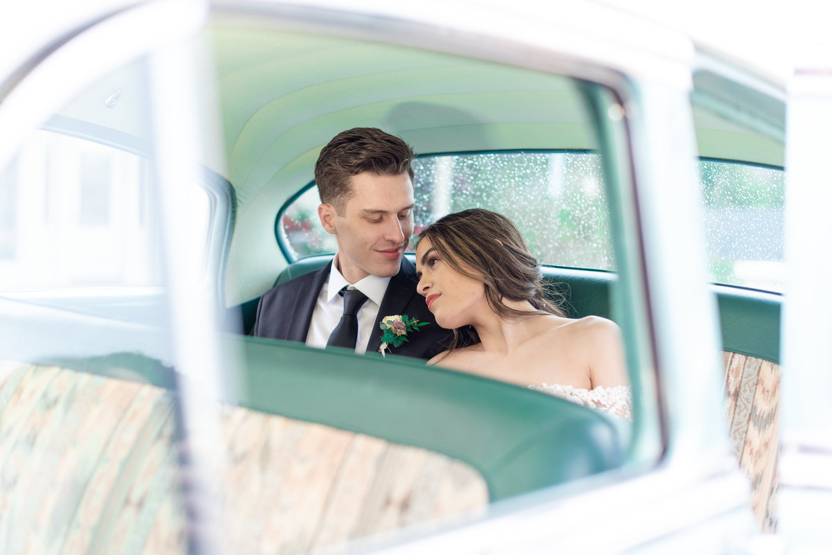 Bride and groom sit in vintage car while bride lays on grooms shoulder