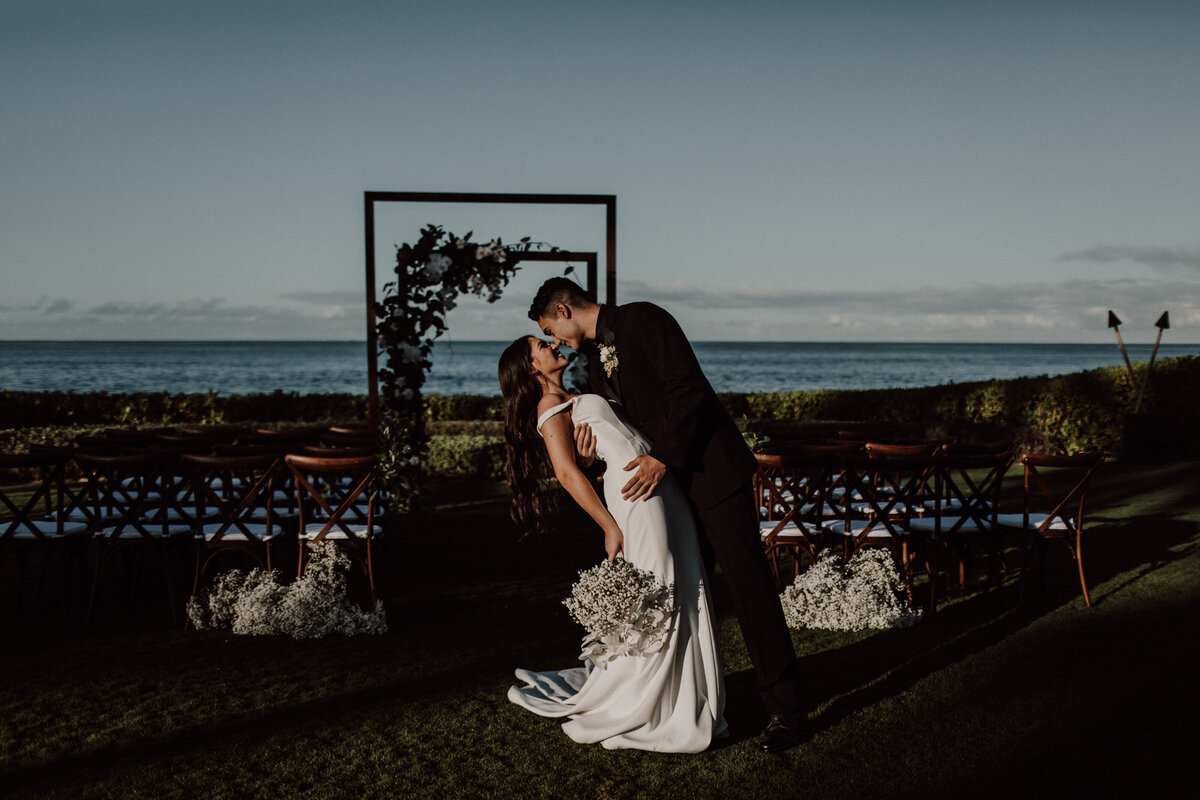 Groom dip kissing bride in front of floral covered ceremony arch with the ocean in the background