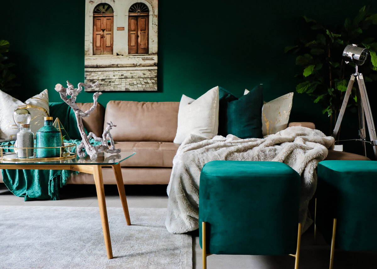 Dark green painted walls create a boho loung with a tan leather sofa and a beige throw.
