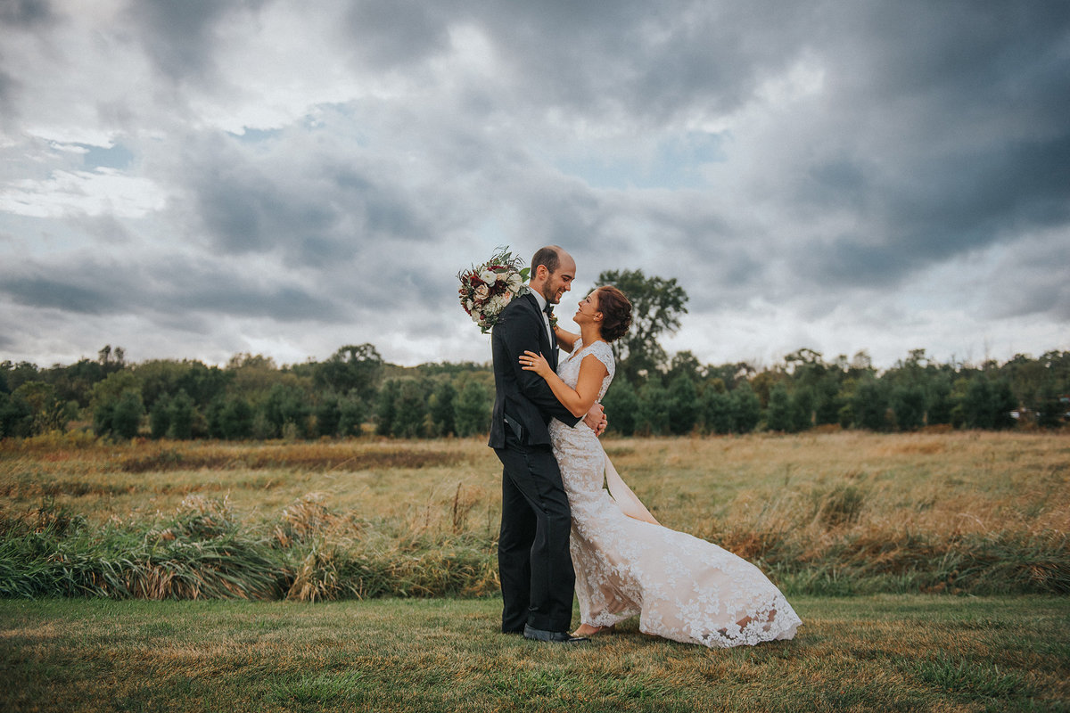 Bride and Groom embracing under cloudy stormy sky