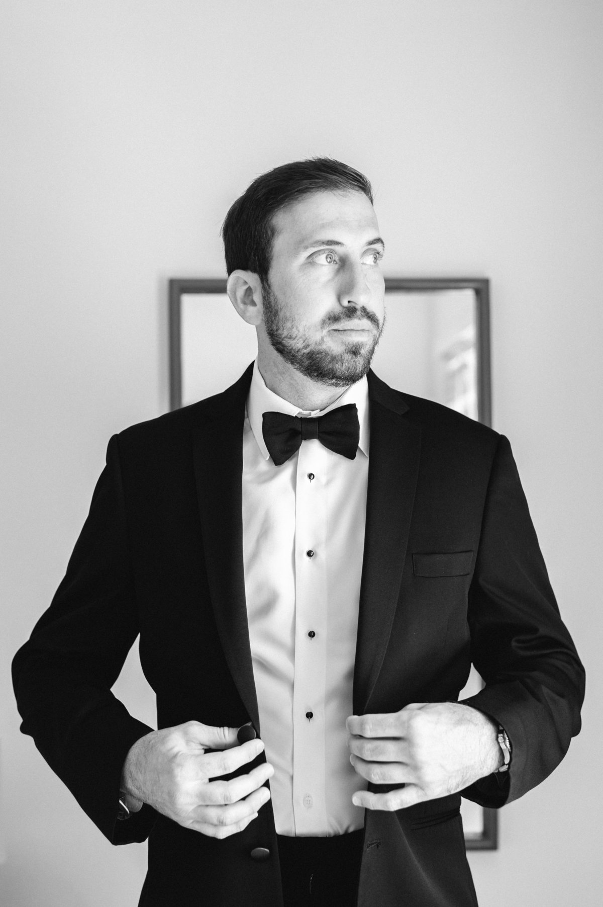 groom buttoning coat wearing black bow tie