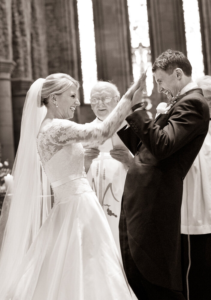 bride wearing a ballgown style dress with statement lace, long sleeves giving a high five to her groom after exchanging the rings in Killarney cathedral