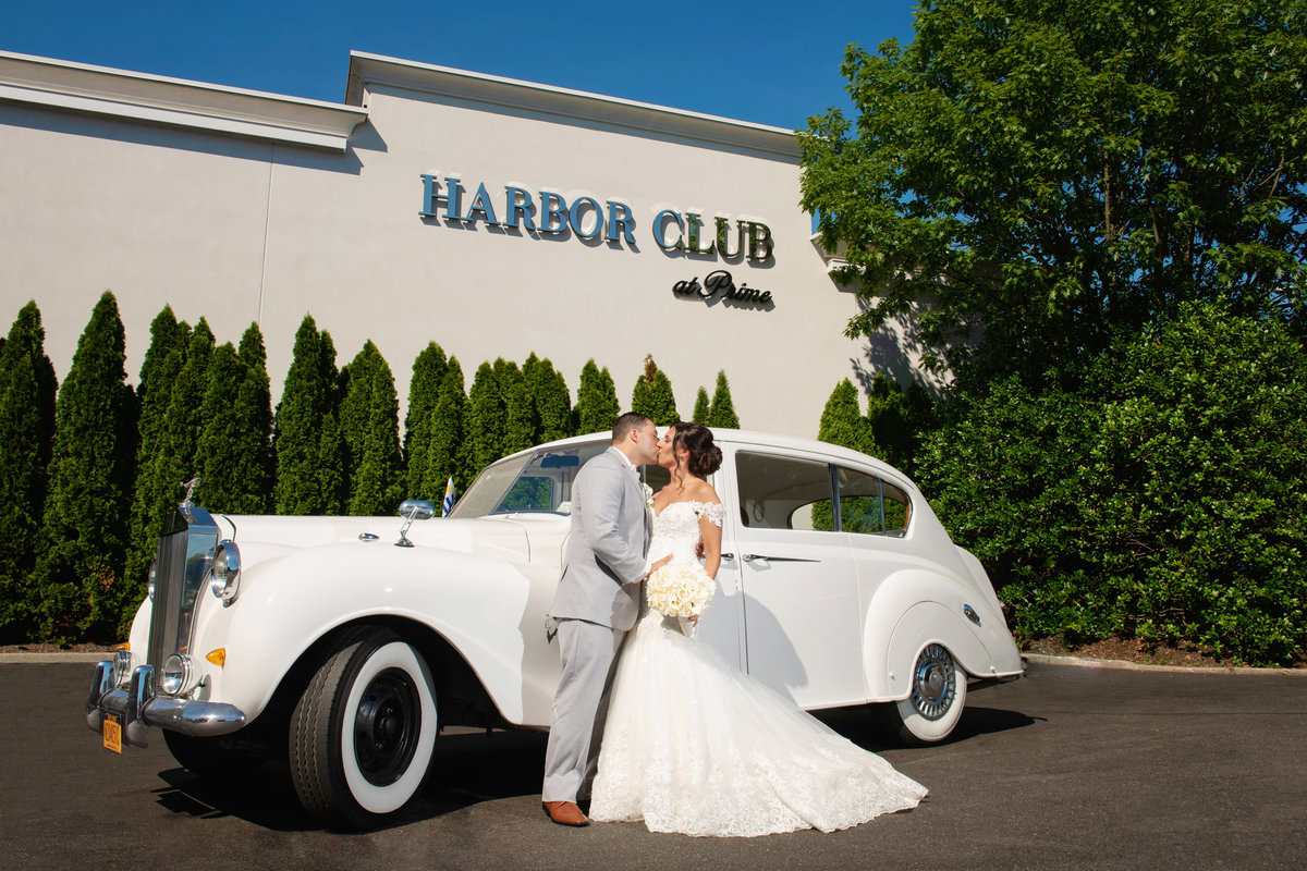 Bride and groom outside the sign of Harbor Club at Prime