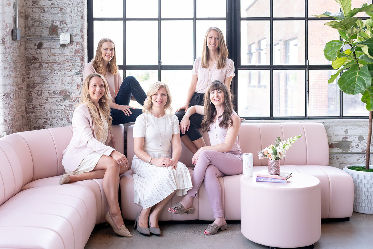 Her Story of Success team sitting on pink couch