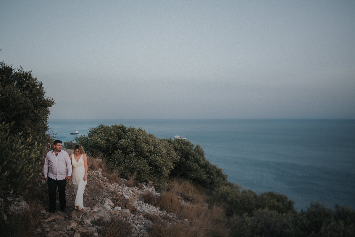 Gibraltar Wedding Photographer captures newly married couple walking hand in hand on 'The Rock' with views of Africa in the background