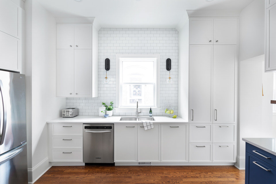 White and blue kitchen with subway tiled wall