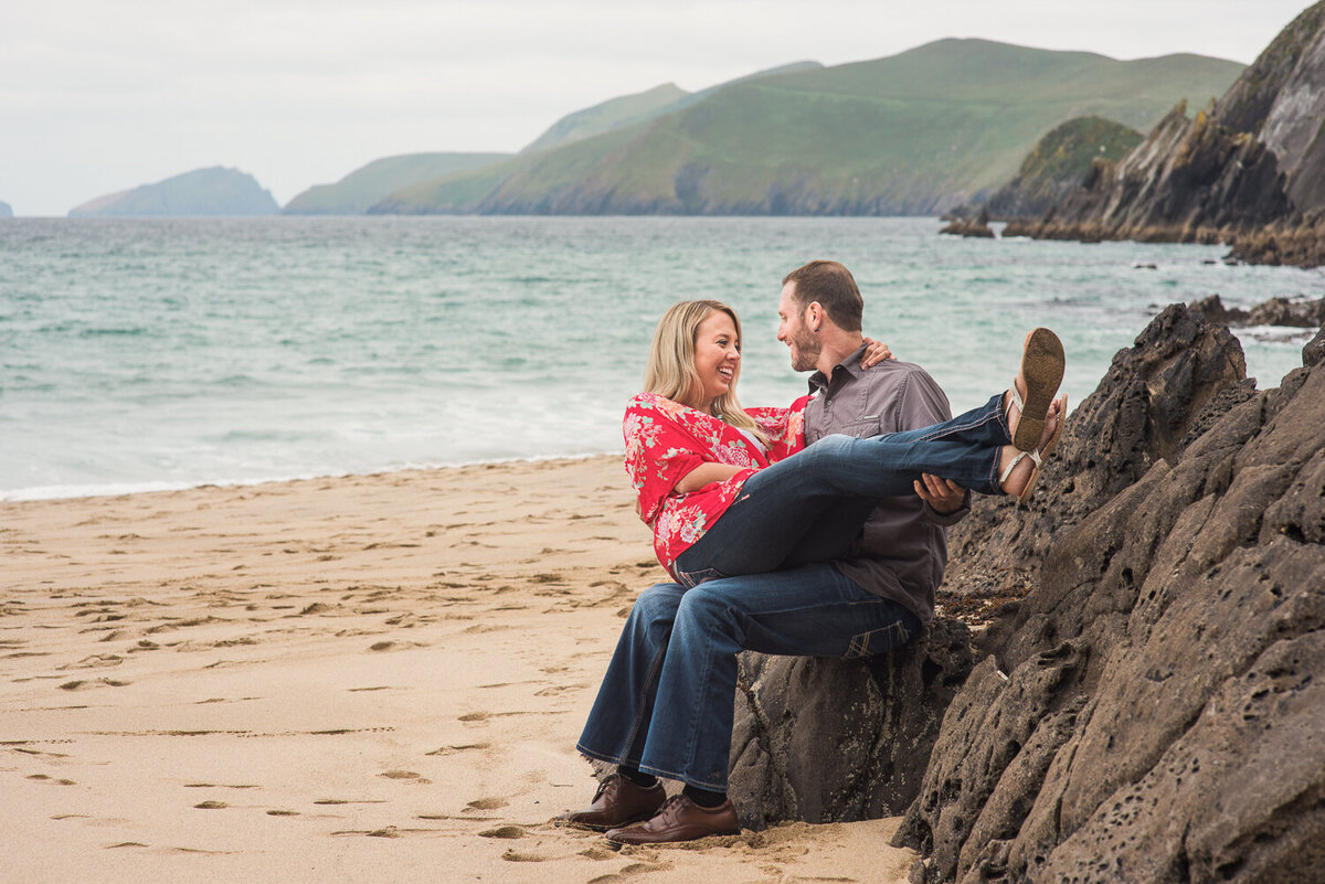 engaged couple wearing denim sitting on a rock on the beach in Dingle having fun