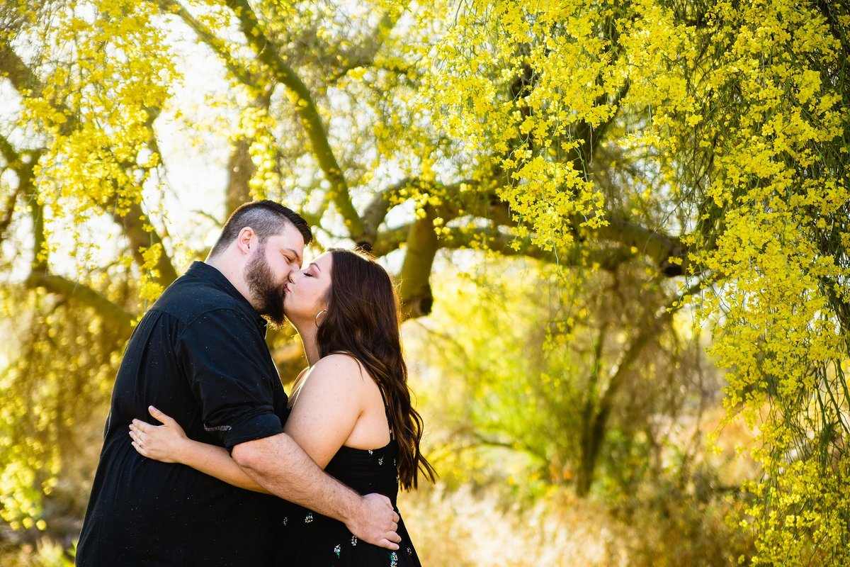 Couple kissing in front of blooming palo verde trees during their Spring engagement session by Phoenix engagement photographer PMA Photography.
