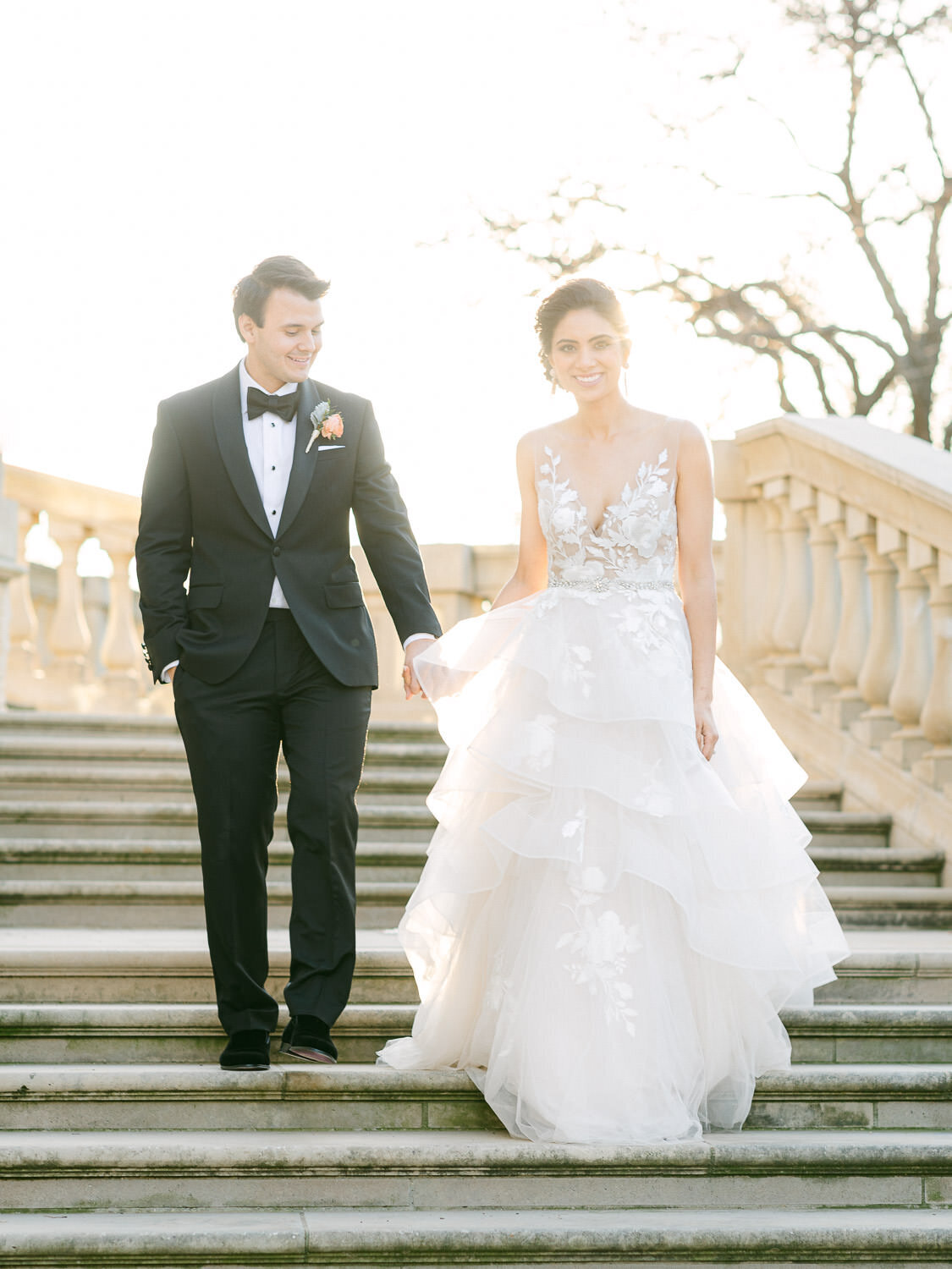 smiling bride and groom walking down concrete stairs at sunset