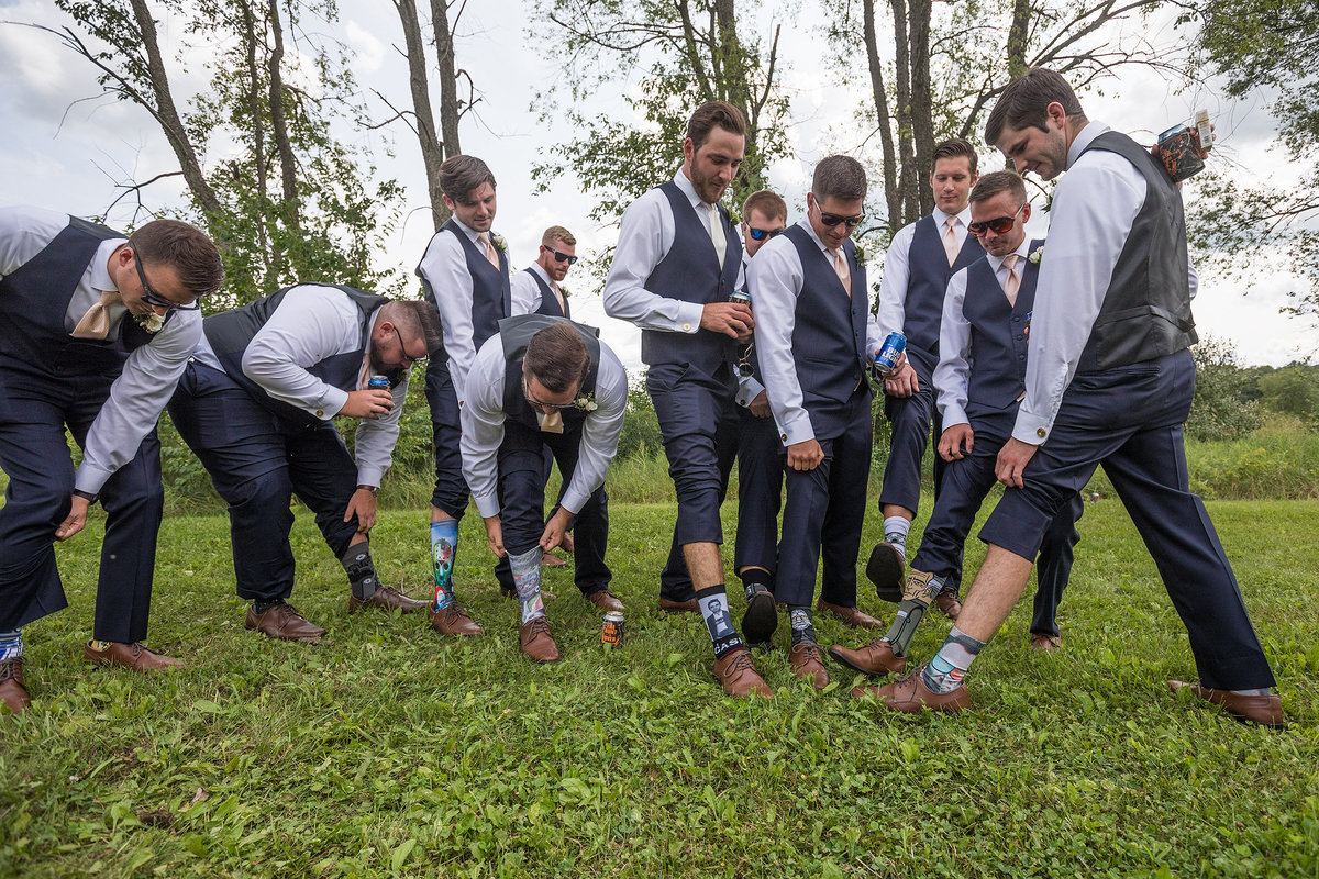 groomsmen showing off their socks at a wedding