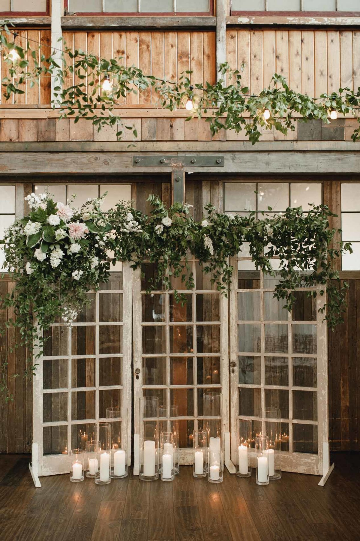 These reclaimed french doors that we covered in greens and cafe au lait dahlias make a striking wedding ceremony backdrop.