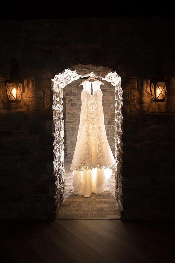 A dramatic photo of a wedding dress hanging  in the doorway of a stone wine cellar