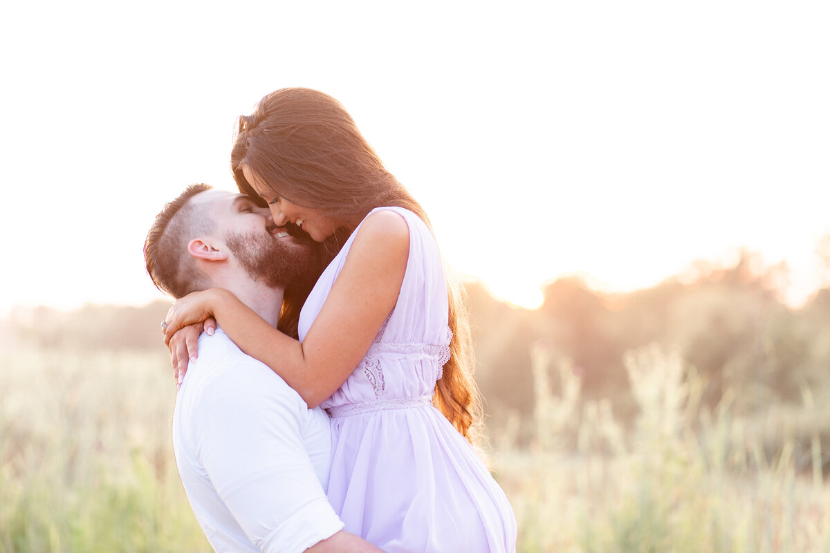 Summer Sunset Romantic Engagement Session guy lifting girl in lavender maxi dress in field on dirt road at Busch Wildlife in St. Louis by Amy Britton Photography Photographer in St. Louis