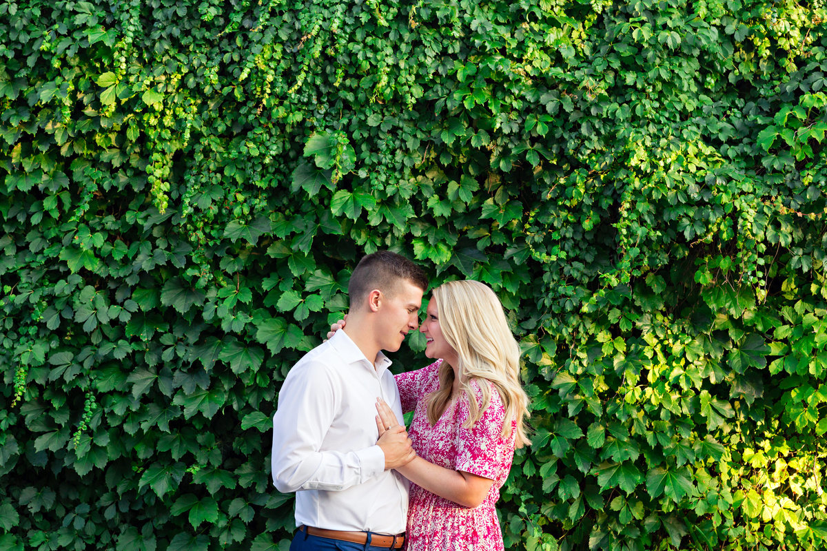The couple hold each other close in front of the ivy wall in Portsmouth NH