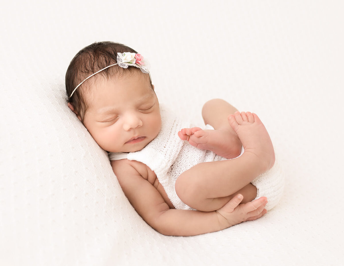 Newborn girl posed at our Rochester, Ny studio.