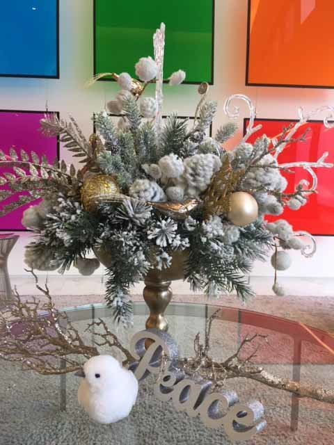 white winter centerpiece in gold orn with flocked evergreens, peace sign, white bird, gold and silver ornaments