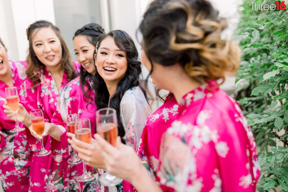 Bride and her Bridesmaids share a glass of Champaign  before getting dressed