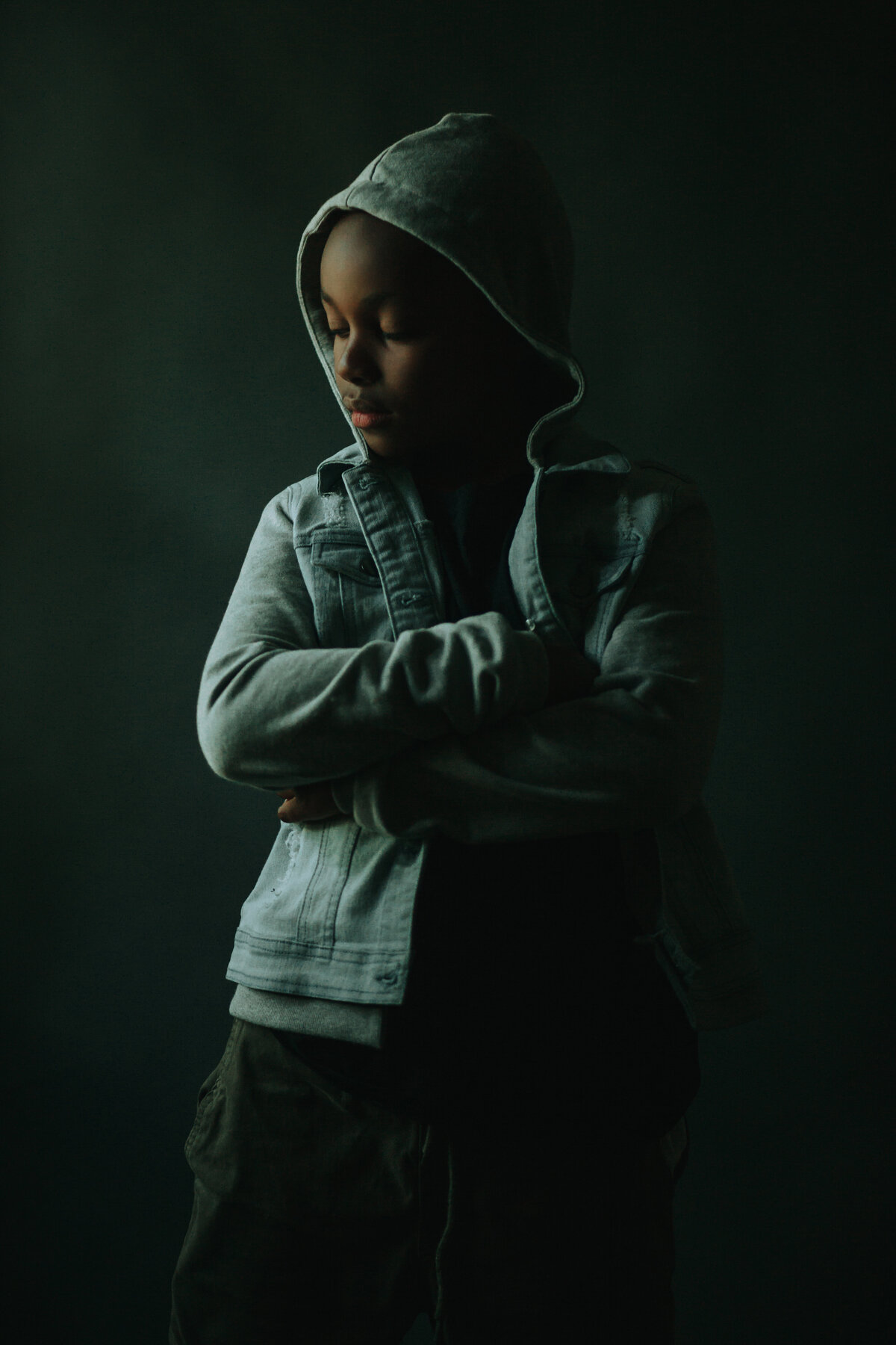 Portrait of a boy in a hooded jacket, arms crossed, looking camera left.