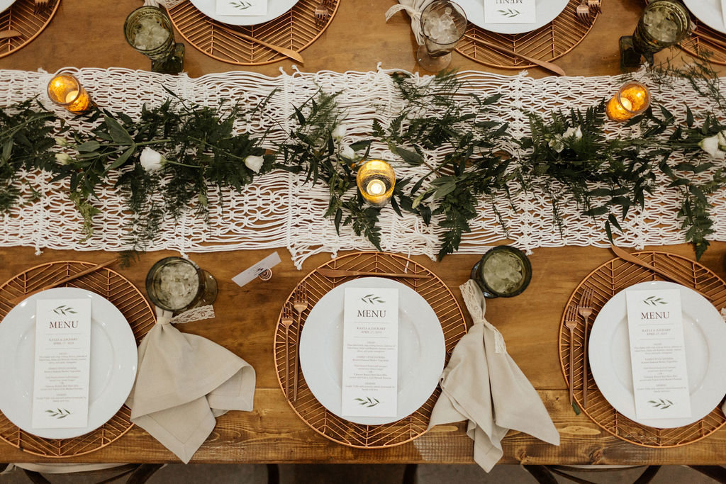 Farm table with copper chargers macrame and greenery tablescape