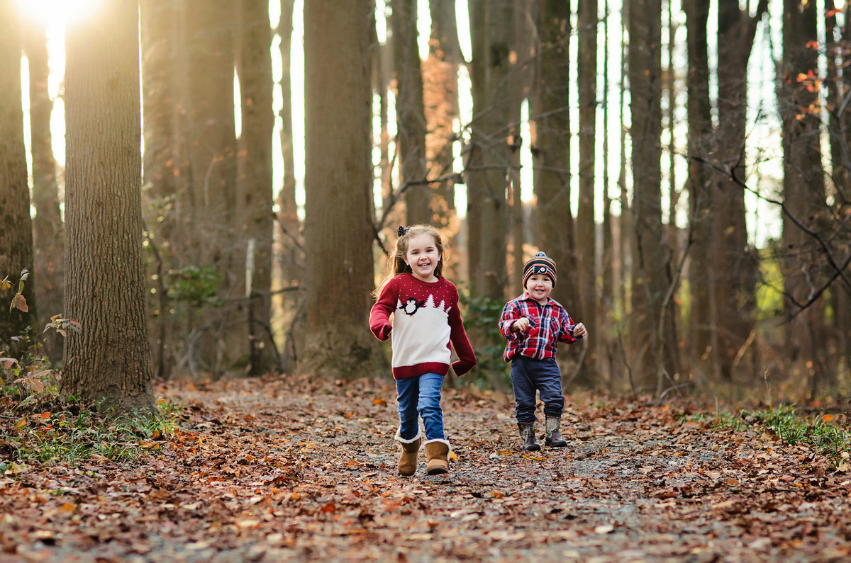 Portrait of a sister and brother running during a family session at Nottoway Park in Norther Virginia taken by Sarah Alice Photography