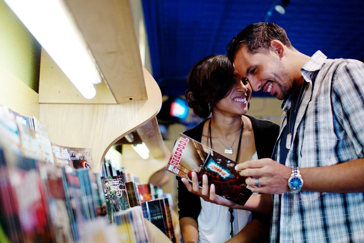a man reads deadpool comic in a colorful book shop while his girlfriend looks and laughs during their engagement portraits