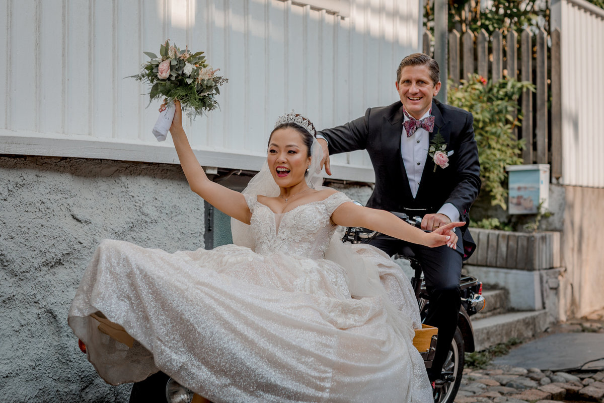 A bridal couple sitting on a motorbike having fun.