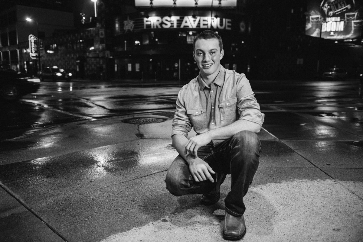 Senior boy sitting in front of First Avenue in Minneapolis, Minnesota