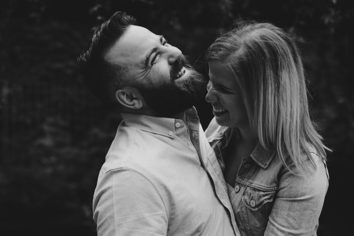 engaged couple laughing together in black and white