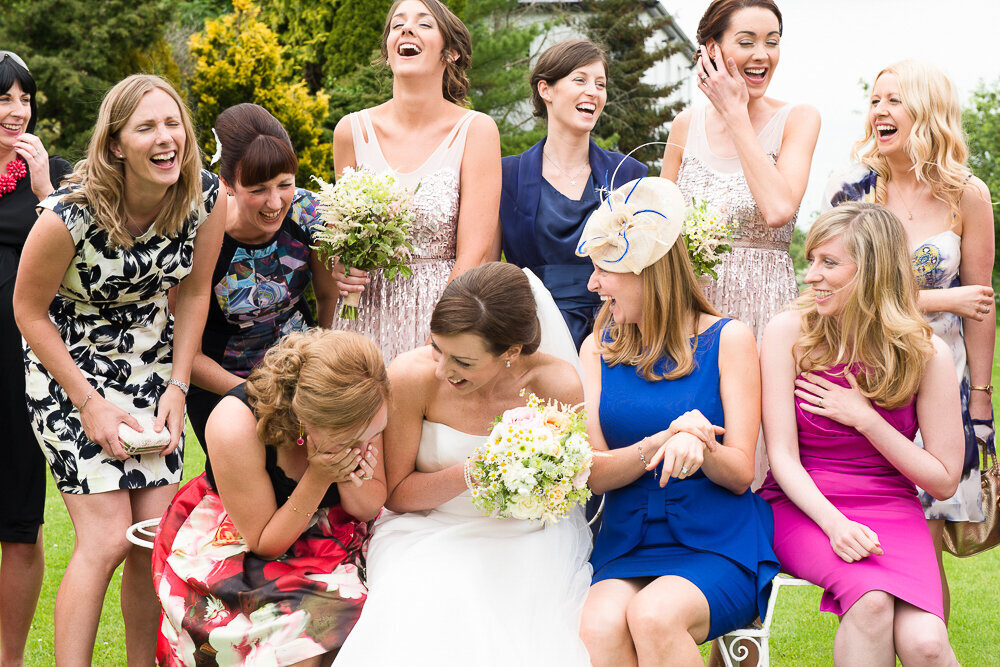 Bride in A-line wedding dress holding white flower bouquet sitting with friends in garden laughing