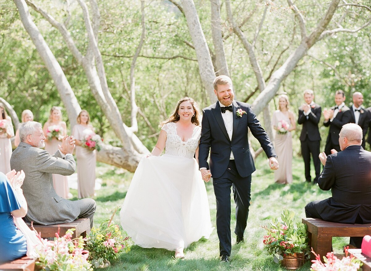 Bride and groom walk down the aisle at gardener ranch