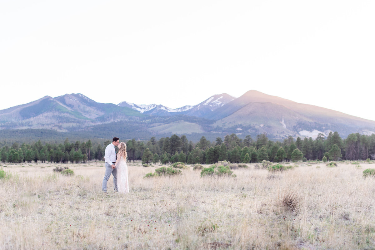 eloped bride and groom hold hands in front of mountain in flagstaff arizona