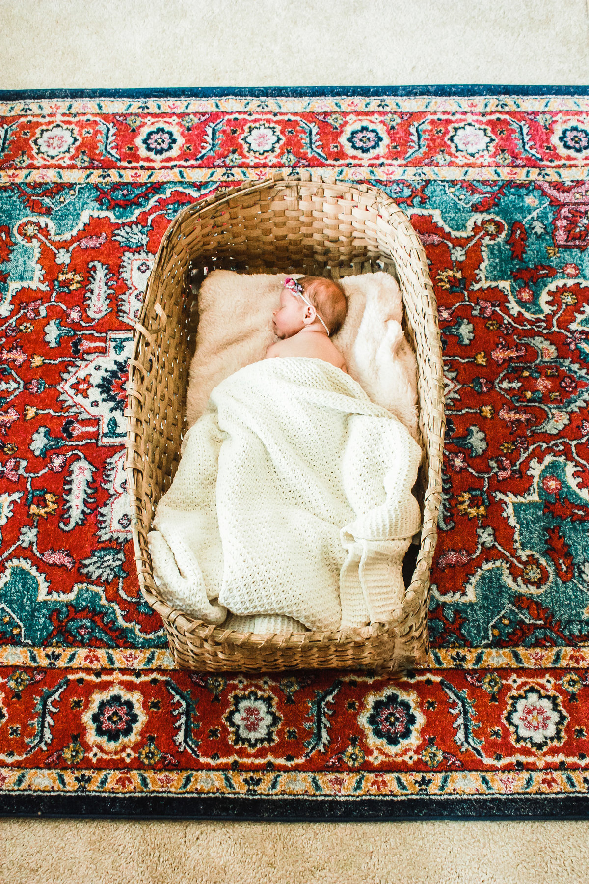 In-home newborn session, colorful rug, little girl, in a basket