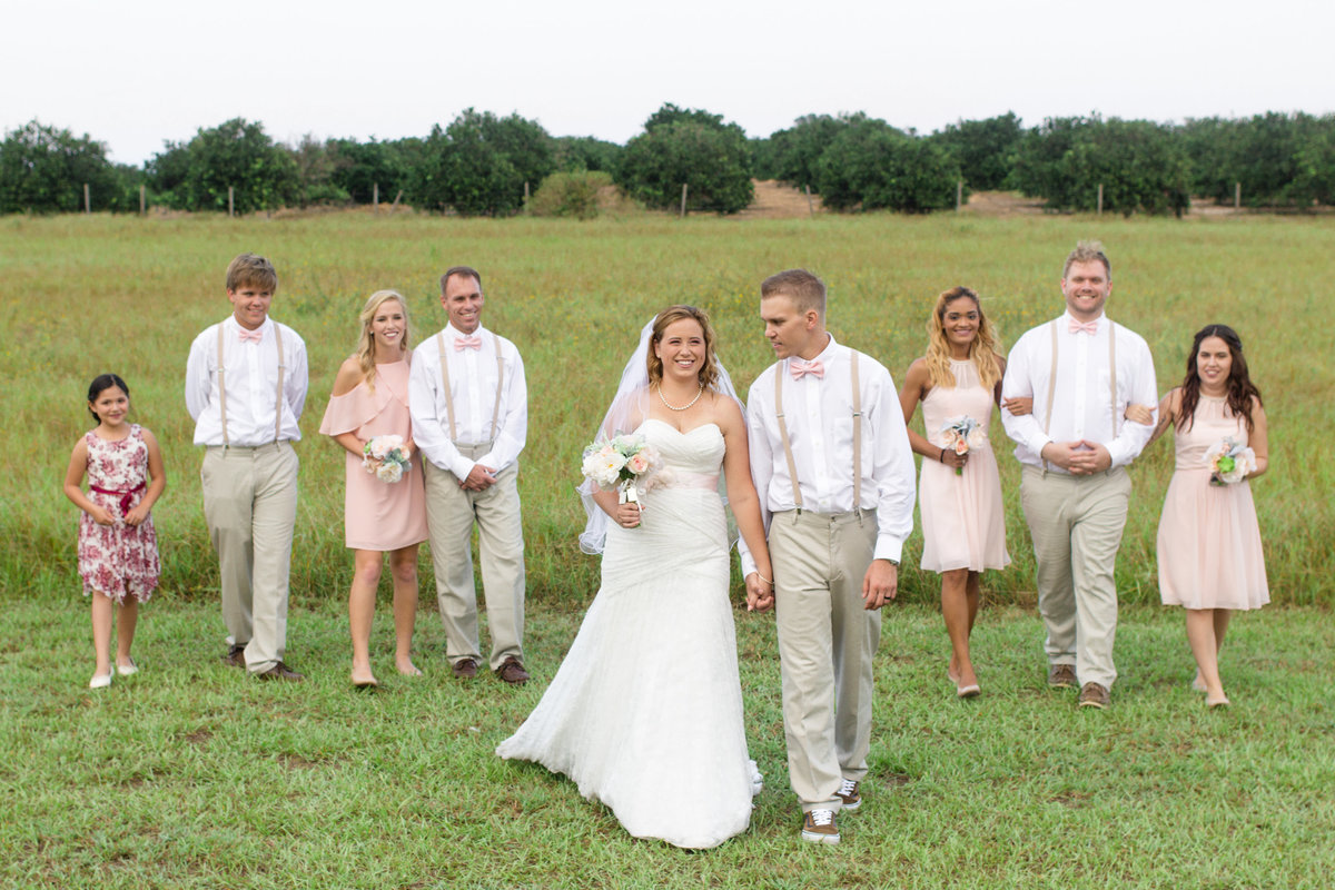 Bridal party in blush, white and khaki walk smiling behind bride and groom as they hold hands on their wedding day in Orlando, Florida