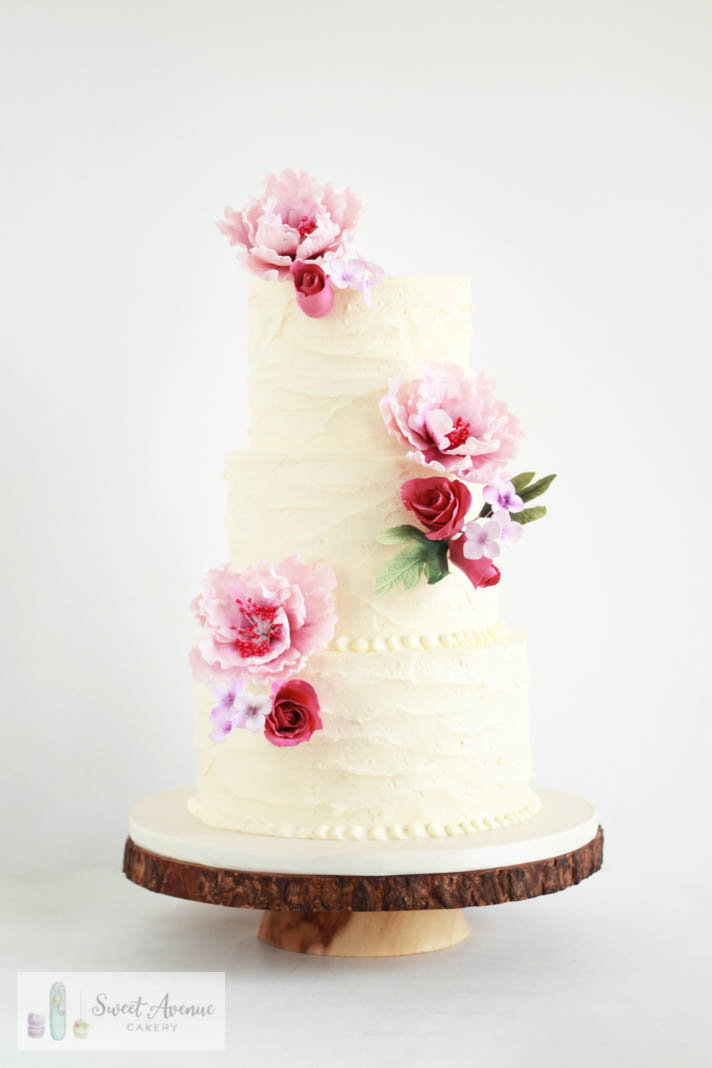 rustic textured buttercream wedding cake with pink peonies and roses