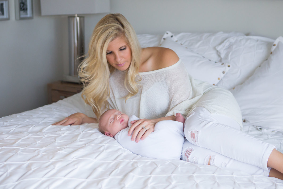 Mother cuddling newborn baby son on bed {Milton Family Photographer}