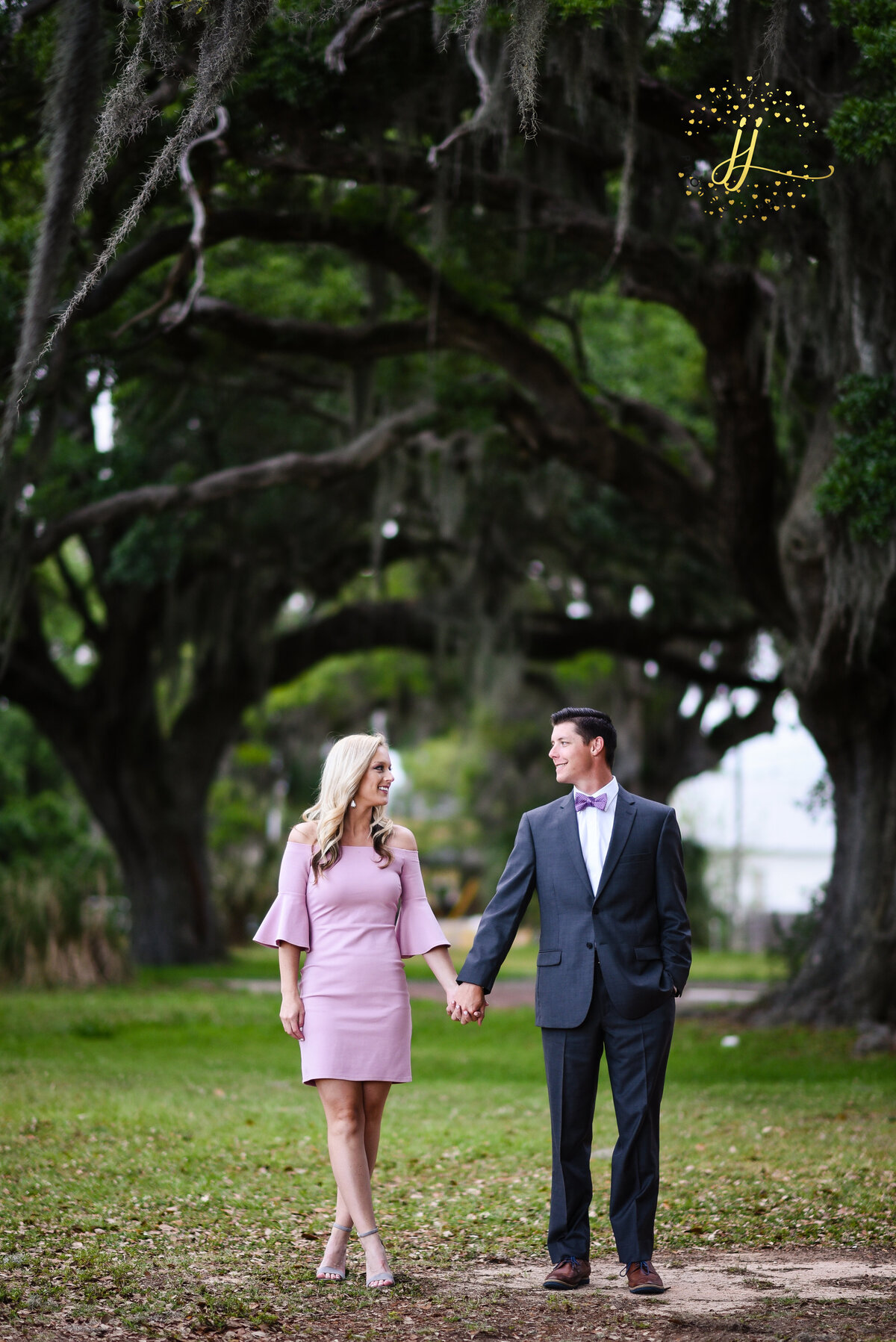Beautiful Mississippi Engagement Photography: couple walks holding hands under oaks with Spanish Miss in Ocean Springs, MS