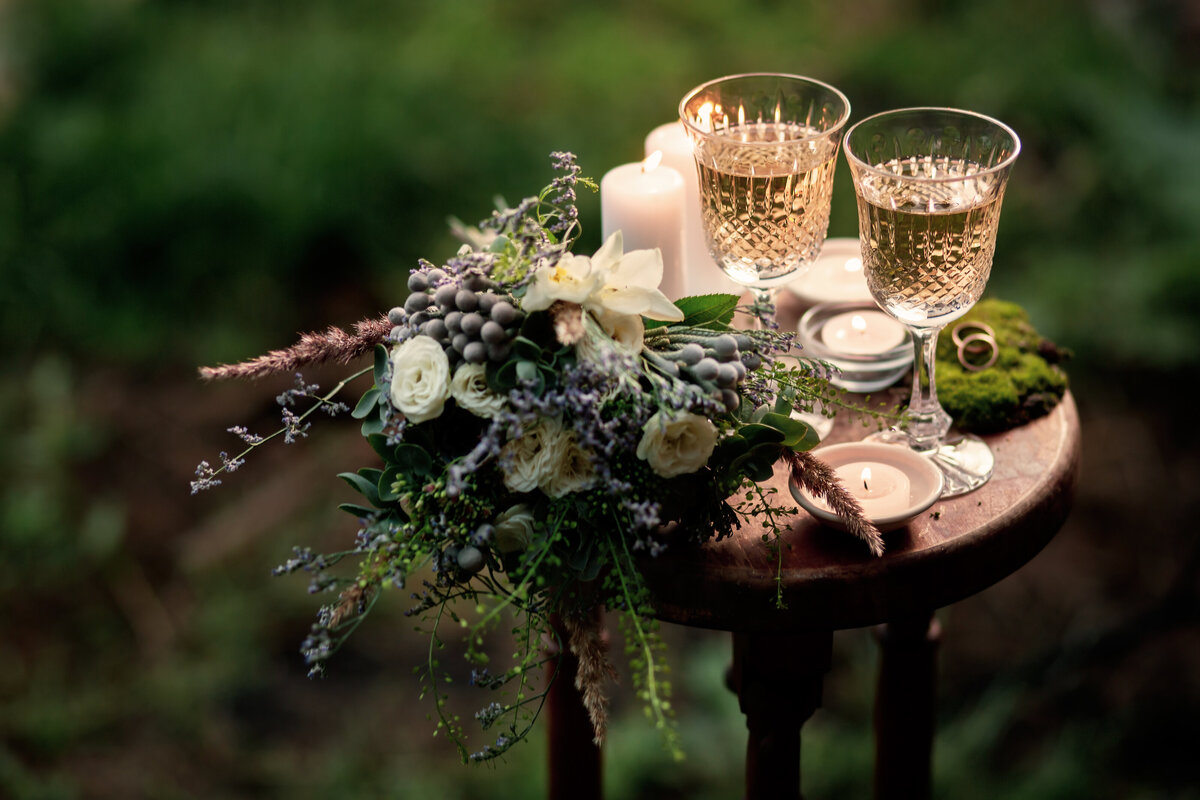 Vintage wedding background with bouquet, wine glasses and candles outdoors